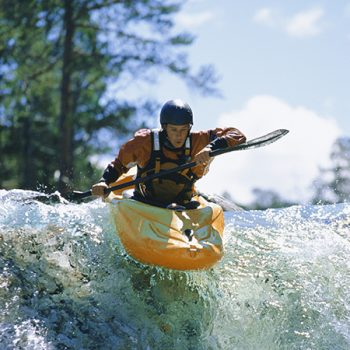 Young man kayaking on waterfall